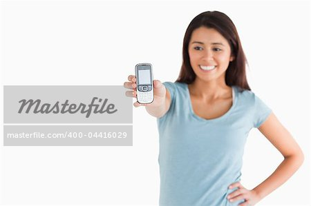 Lovely woman showing her mobile phone while standing against a white background Stock Photo - Budget Royalty-Free, Image code: 400-04416029