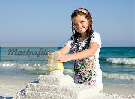 Happy girl building sandcasttle on a beach