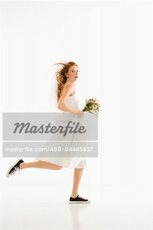 Caucasian bride running and holding bouquet. Stock Photo - Budget Royalty-Free, Image code: 400-04445617