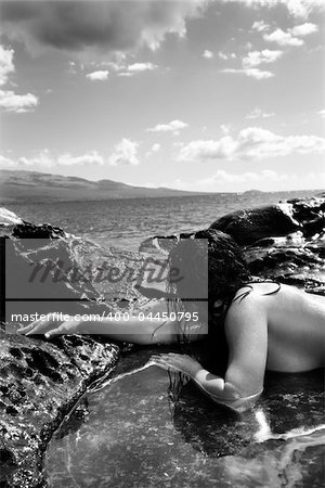 Close up of nude Caucasian mid adult woman lying in tidal pool at Maui coast looking toward ocean. Stock Photo - Budget Royalty-Free, Image code: 400-04450795