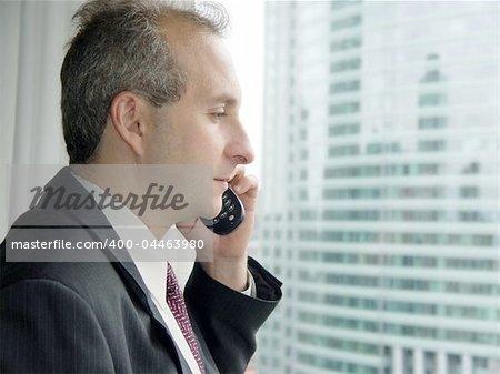 Businessman by the window talking on the phone Stock Photo - Budget Royalty-Free, Image code: 400-04463980