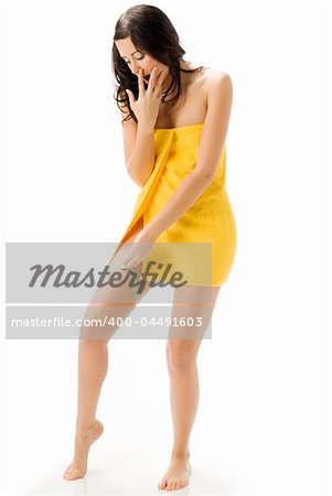 pretty young brunette wearing a yellow towel and measuring her legs making funny face Stock Photo - Budget Royalty-Free, Image code: 400-04491603