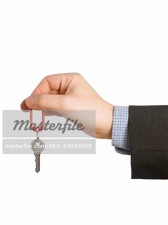 A hand holding a red keyring with a blank label and a key.