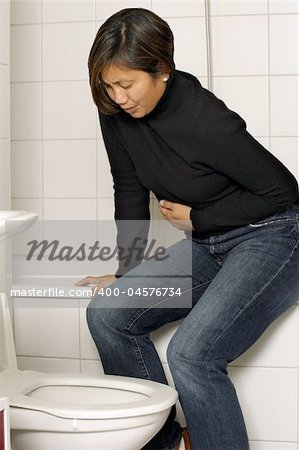 Asian woman with stomach sickness about to vomit into her toilet. Stock Photo - Budget Royalty-Free, Image code: 400-04576734
