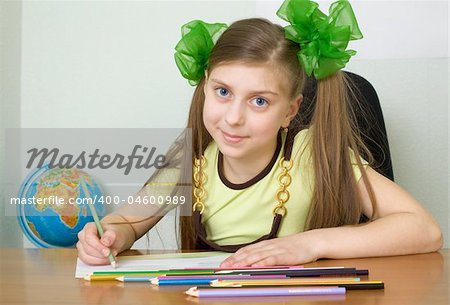 The girl sitting at a table with color pencils