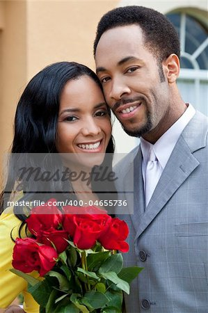A romantic and happy African American man and woman couple in their thirties smiling together with a bunch of roses. Stock Photo - Budget Royalty-Free, Image code: 400-04655736