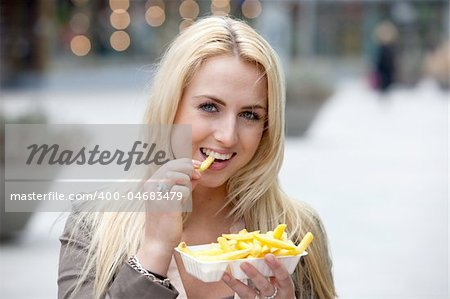 Pretty blond girl eating fries with mayonnaise Stock Photo - Budget Royalty-Free, Image code: 400-04683479