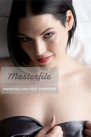 Sexy naked young caucasian adult woman with red lips, short black hair and a pierced eyebrow, covered in a dark satin sheet and sitting on a bed Stock Photo - Budget Royalty-Free, Image code: 400-04690599
