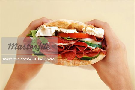 appetizing big fresh sandwich with ham, cheese and vegetables in hands Stock Photo - Budget Royalty-Free, Image code: 400-04696265