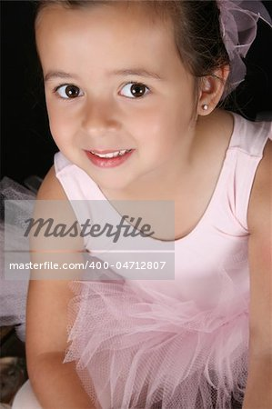 Cute little ballet girl wearing a tutu looking up at the camera Stock Photo - Budget Royalty-Free, Image code: 400-04712807