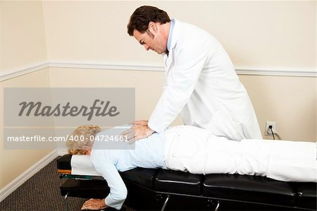 Chiropractor adjusting a senior woman's back.  Room for text Stock Photo - Budget Royalty-Free, Image code: 400-04724661