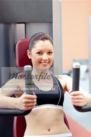 beautiful athletic woman using a bench press smiling at the camera in a fitness center