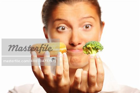 A picture of a young woman trying to decide between healthy and unhealthy food Stock Photo - Budget Royalty-Free, Image code: 400-04737971