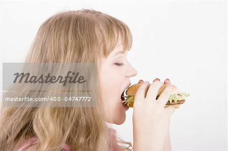 The young woman on a white background bites a hamburger Stock Photo - Budget Royalty-Free, Image code: 400-04747772