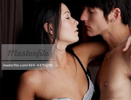 Young adult Caucasian couple in passionate embrace and undressing each other during sexual foreplay Stock Photo - Budget Royalty-Free, Image code: 400-04751285