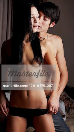 Young adult Caucasian couple in passionate embrace and undressing each other during sexual foreplay Stock Photo - Budget Royalty-Free, Image code: 400-04751287