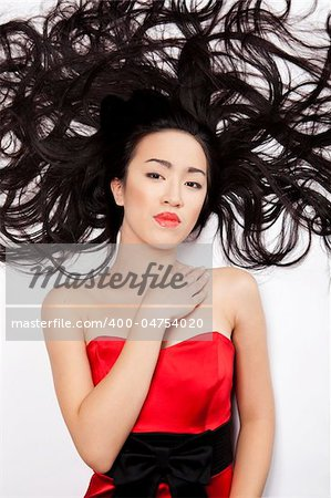beautiful Chinese woman lying down on the floor with long hair