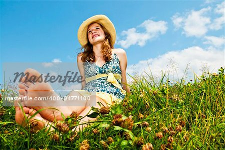 Young teenage girl sitting on summer meadow barefoot Stock Photo - Budget Royalty-Free, Image code: 400-04771100