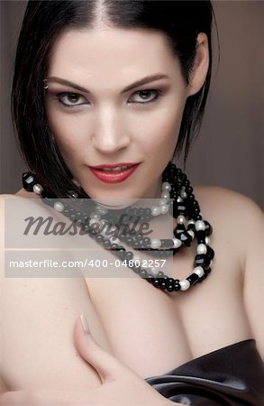 Sexy naked young caucasian adult woman with red lips, short black hair and a pierced eyebrow, covered in a dark satin sheet and wearing a black and white pearl string necklace Stock Photo - Budget Royalty-Free, Image code: 400-04802257