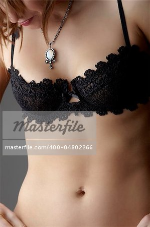Young adult caucasian woman wearing black lace lingerie on a neutral grey background. Stock Photo - Budget Royalty-Free, Image code: 400-04802266