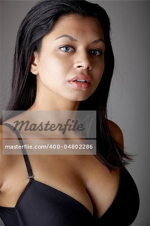 Young voluptuous Indian adult woman with long black hair wearing black lingerie and blue coloured contact lenses on a neutral grey background. Mixed ethnicity Stock Photo - Budget Royalty-Free, Image code: 400-04802286