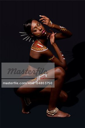 Beautiful exotic African female fashion with tribal yellow red and white makeup cosmetics and sticks in hair, in cultural dance position. Stock Photo - Budget Royalty-Free, Image code: 400-04803750