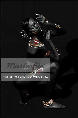Beautiful exotic African female fashion with tribal yellow red and white makeup cosmetics and sticks in hair, in cultural dance position. Stock Photo - Budget Royalty-Free, Image code: 400-04803751