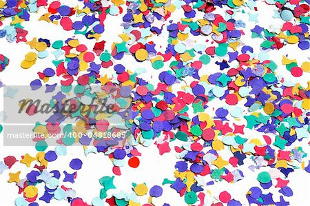 a pile of confetti of different colors on a white background