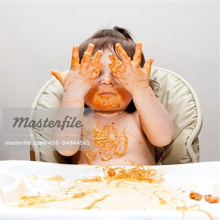 Happy baby having fun eating messy showing hands covered in Spaghetti Angel Hair Pasta red marinara tomato sauce. Stock Photo - Budget Royalty-Free, Image code: 400-04844561