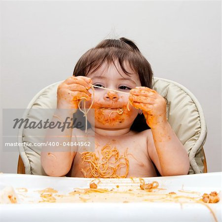 Happy baby having fun eating messy covered in Spaghetti holding Angel Hair Pasta red marinara tomato sauce. Stock Photo - Budget Royalty-Free, Image code: 400-04844562