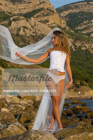 Beautiful bride in a corset is on the rock Stock Photo - Budget Royalty-Free, Image code: 400-04845191