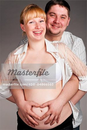 happy husband is embracing his pregnant wife with heart shape made of fingers Stock Photo - Budget Royalty-Free, Image code: 400-04866560