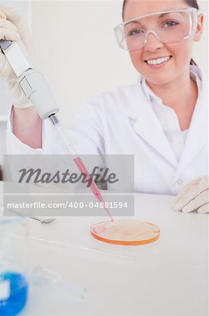 Attractive red-haired scientist using a pipette in a lab