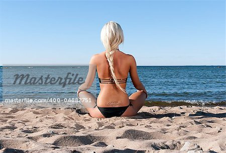 blonde girl in a black bathing suit sits with his back to the beach in the sand and meditate