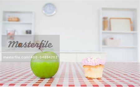 An apple and a cupcake on a tablecloth in a kitchen Stock Photo - Budget Royalty-Free, Image code: 400-04884202
