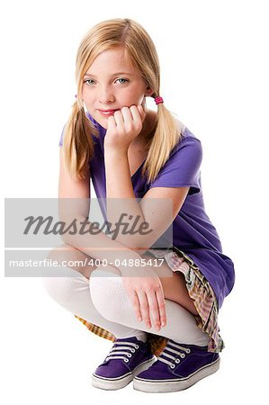 Beautiful happy teenage girl sitting squatted wearing knee socks, puple sporty shoes, shirt and colorful skirt, hand supporting her head, isolated. Stock Photo - Budget Royalty-Free, Image code: 400-04885417