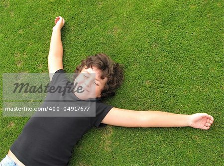 Happy child resting on a beautiful green grass Stock Photo - Budget Royalty-Free, Image code: 400-04917677