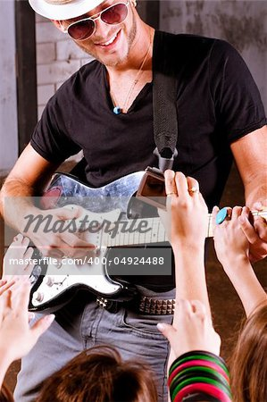 Rock guitarist playing in front of a cheering crowd. Stock Photo - Budget Royalty-Free, Image code: 400-04924488