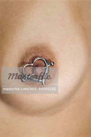 Multi ethnic young adult female breast with heart shaped nipple ring. Stock Photo - Budget Royalty-Free, Image code: 400-04955225