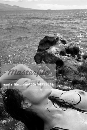 Topless Caucasian mid adult woman on rocky Maui coast lying on back with eyes closed. Stock Photo - Budget Royalty-Free, Image code: 400-04955639