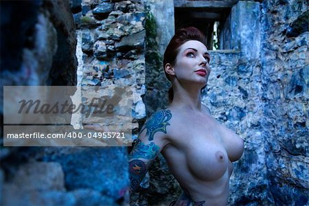 Blue-toned portrait of tattooed sexy nude Caucasian woman next to concrete wall. Stock Photo - Budget Royalty-Free, Image code: 400-04955721