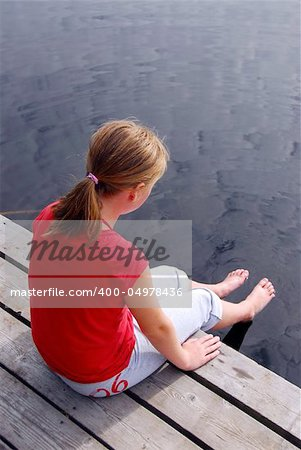 Young girl sitting on the edge of boat dock dipping her feet in water