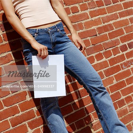 Fashionable girl against red brick wall with blank paper. Stock Photo - Budget Royalty-Free, Image code: 400-04998337