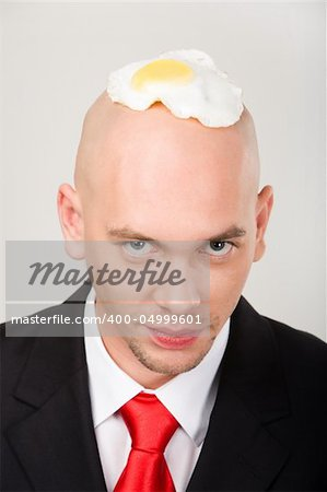 Bald man with fried eggs on top of head looking at camera Stock Photo - Budget Royalty-Free, Image code: 400-04999601