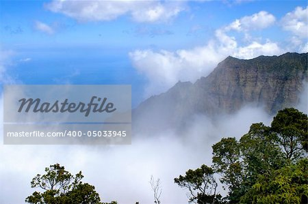 Beautiful Na Pali Coast is hugged by a large white cloud.  Vivid blue sky and water below. Stock Photo - Budget Royalty-Free, Image code: 400-05033945