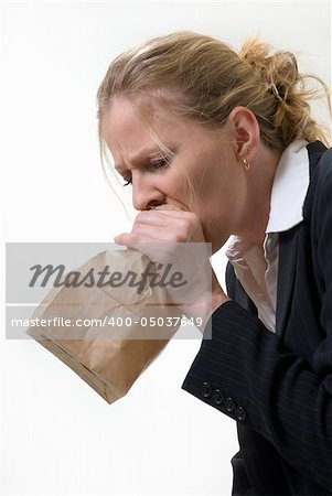 Blond woman holding a brown paper bag over mouth with a distraught expression as if having a panic attack or being nauseated Stock Photo - Budget Royalty-Free, Image code: 400-05037649