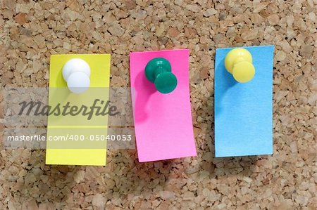 Close up from colorful blank post it note affixed to the corkboard.