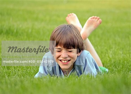 Boy Laying in the Grass Laughing Hard Stock Photo - Budget Royalty-Free, Image code: 400-05042979