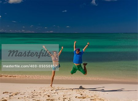 Young couple jumping on white sand beach by turquoise waters on tropical island Stock Photo - Budget Royalty-Free, Image code: 400-05050857