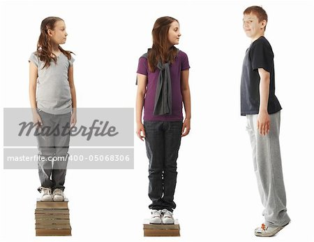 Two smaller girls standing on a pile of books and a boy standing on tiptoe Stock Photo - Budget Royalty-Free, Image code: 400-05068306